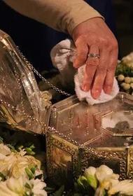 Перед поцелуем святых мощей Иоанна Крестителя в Казанском соборе ковчег протирают спиртом