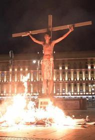 На Лубянке напротив здания ФСБ необычный перфоманс – горящий крест и человек на распятье