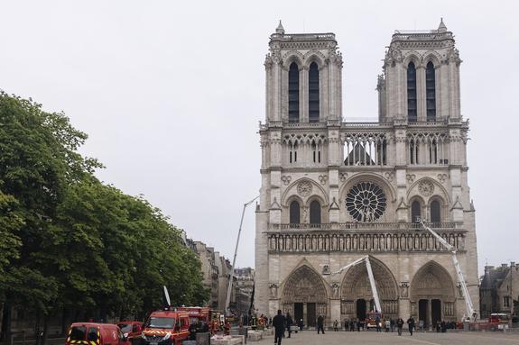Пожарные осматривают левую башню собора Парижской Богоматери после пожара